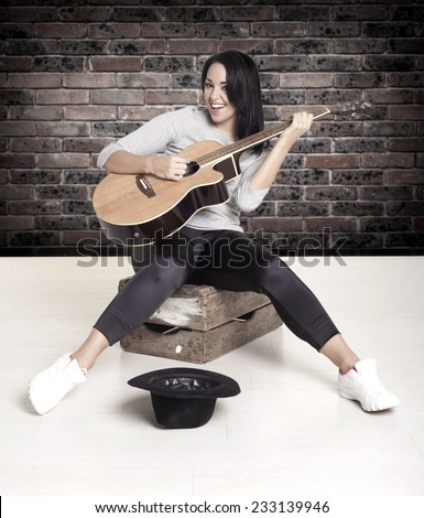 Young female busker sitting on a wooden box playing her guitar for money. - stock photo