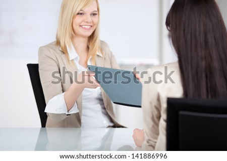 Young female candidate giving file to businesswoman at office desk - stock photo