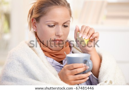 Young female caught cold, feeling bad, wrapped up in blanket, squeezing lemon to her tea.