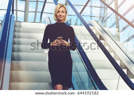 Young Female CEO With Mobile Phone In Hands, Is Using Moving Staircase In  Modern Interior