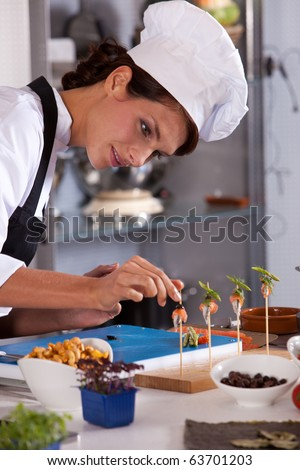 Young female chef adding the finishing touch to her amuse - stock photo