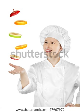 Young female chef catching sliced fruit - stock photo