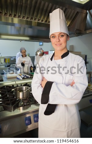 Young female chef holding ladle in the kitchen