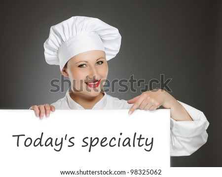 Young female chef showing today's menu - stock photo