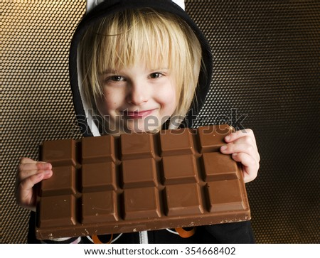 Young female child holding with both hands big chocolate bar in front of her happy smiling face expression in sugary nutrition and kids loving sweet concept. - stock photo