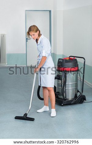 Young Female Cleaner In Uniform Vacuuming Floor