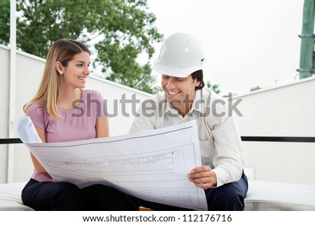 Young female client discussing house plan with male architect - stock photo
