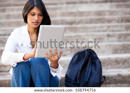young female college student using tablet computer outdoors - stock photo