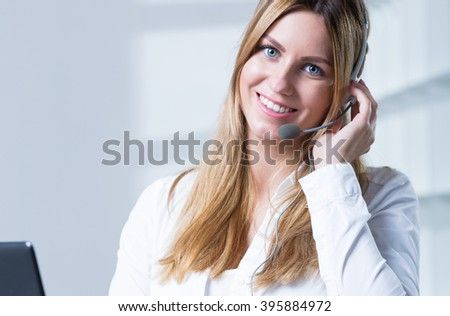 Young female corporation worker in headphones