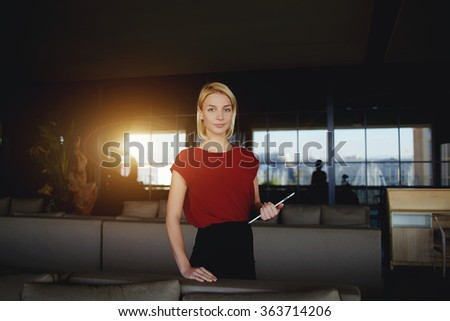 Young female creative designer holding touch pad while standing in modern interior, beautiful successful businesswoman posing with digital tablet while waiting for a partners in luxury restaurant  - stock photo