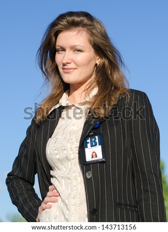 Young female criminalist on a sky background - stock photo