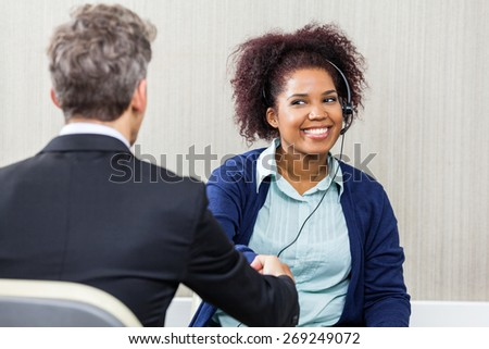 Young female customer service agent wearing headset while shaking hands with manager - stock photo