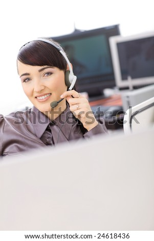Young female customer service operator talking on headset, holding the microphone.