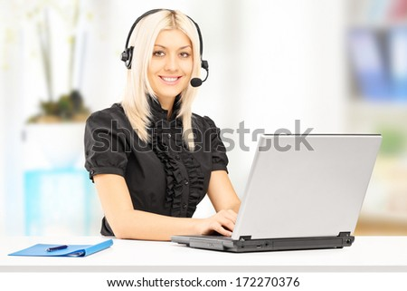 Young female customer service operator working on laptop in office