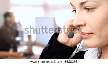 Young female customer service representative receives calls on a headset while an IT specialist works on a computer in the background. - stock photo