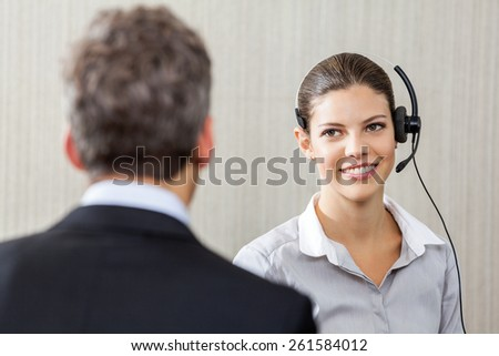 Young female customer service representative wearing headset while looking at manager - stock photo