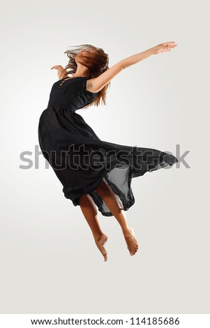 Young female dancer jumping against white background - stock photo