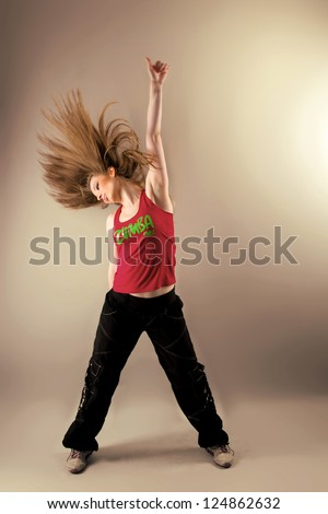 Young female dancing zumba fitness with disheveled hair and a hand raised up in studio