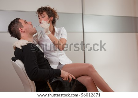 Young female dentist taking care about her patient
