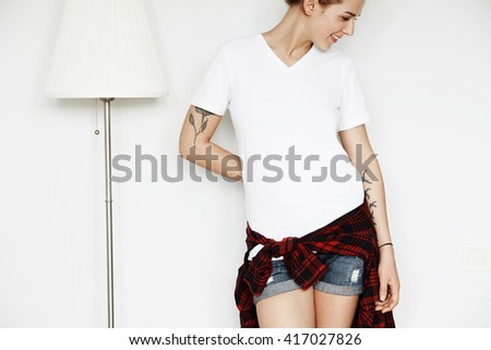 Young female designer trying T-shirt on from her new collection. Confident stylish girl posing against home interior background, looking down with cute smile. Human face expressions and emotions  - stock photo