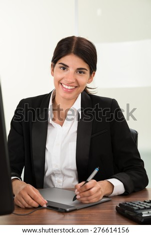Young Female Designer Using Graphic Tablet Sitting At Desk - stock photo