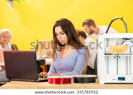 Young female designer using laptop by 3D printer with colleagues in background at studio - stock photo
