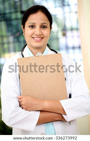 Young female doctor holding clipboard - stock photo