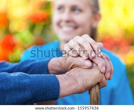 Young female doctor holding his patient hand. - stock photo