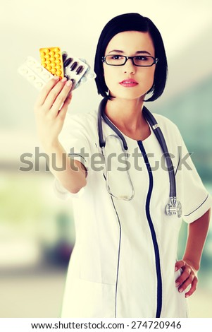 Young female doctor holding pills - stock photo