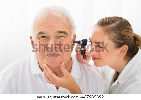 Young Female Doctor Looking At Senior Male Patient's Ear Through Otoscope