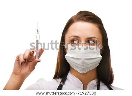 Young female doctor looking at syringe - stock photo