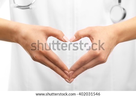 Young female doctor making heart with hand, close up