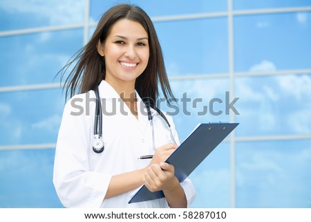 Young female doctor stand against a hospital building - stock photo