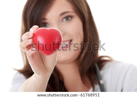 Young female doctor with heart in her hand.  Isolated on white