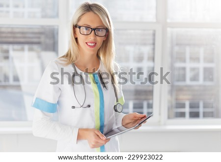 Young female doctor with tablet computer - stock photo