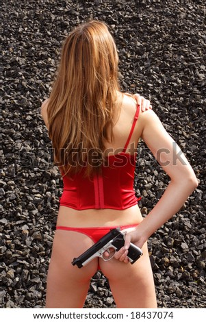 young female dressed in red corset posing with gun - stock photo