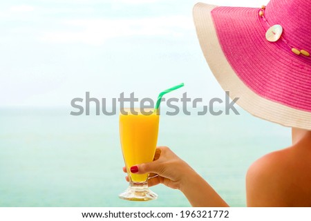 Young female, drinking orange juice, on the beach.