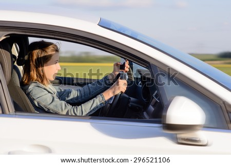 Young Female Driver Driving a White Car on the Road with Focused Facial Expression. - stock photo