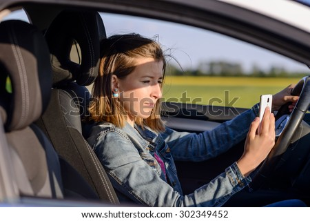 Young female driver reading a text message on her mobile phone as she drives along a rural road, distracting her attention from the road - stock photo