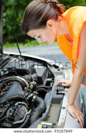 Young female driver wearing a high visibility vest, bending over the engine of her broken down car - stock photo