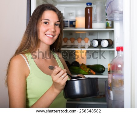 Young female eating from pan near refrigerator at home  - stock photo