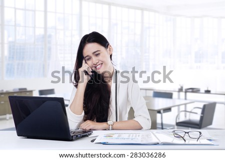Young female entrepreneur doing her job in the office while talking on the mobile phone