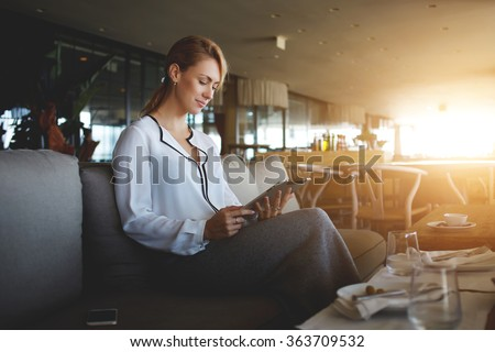 Young female entrepreneur reading electronic book on digital tablet during lunch in modern restaurant interior, elegant businesswoman chatting on touch pad while sitting in comfortable coffee shop - stock photo