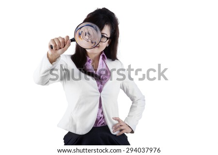 Young female entrepreneur using a magnifier to look at the camera, isolated on white - stock photo