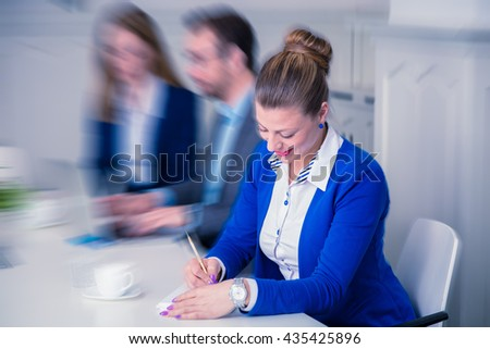 Young female executive taking notes and smiling during the business meeting in the conference room. - stock photo