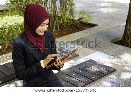 Young female executive using tablet touchscreen outdoor