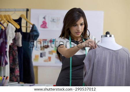 Young female fashion designer working on garment on dressmaker's model