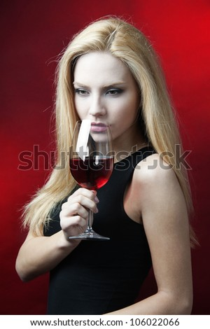 young female fashion model holding wine glass full of red wine at red background - stock photo