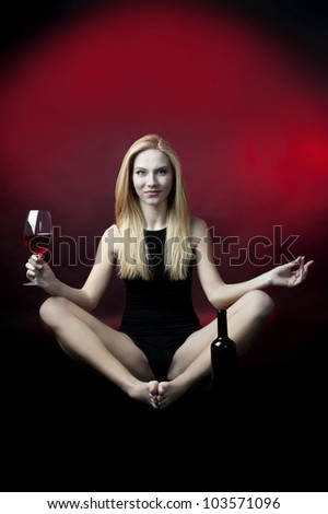 young female fashion model posing with wineglass full of red wine - stock photo