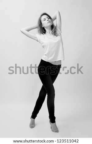 young female fashion model with blond hair wearing jeans and t-shirt